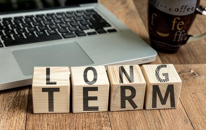 Long Term written on a wooden cube in a office desk