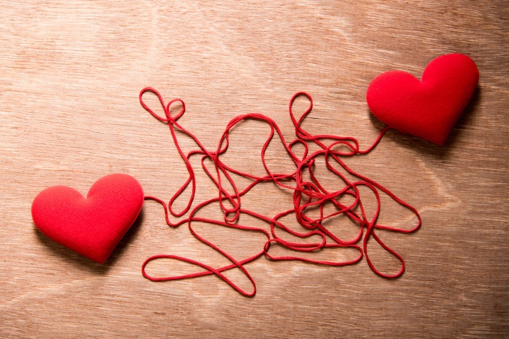 two red heart and complex red string connect together on wood background, love concept